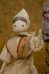 Iowa Corn Husk Doll Sitting on Wood Bench (Close Up)