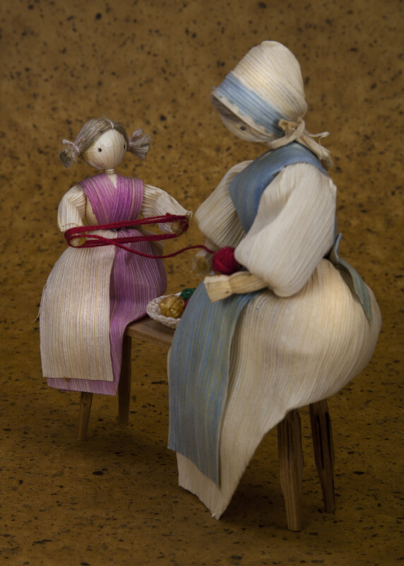 Iowa Corn Husks Dolls Sitting on Bench with Balls of Yarn (Profile View)