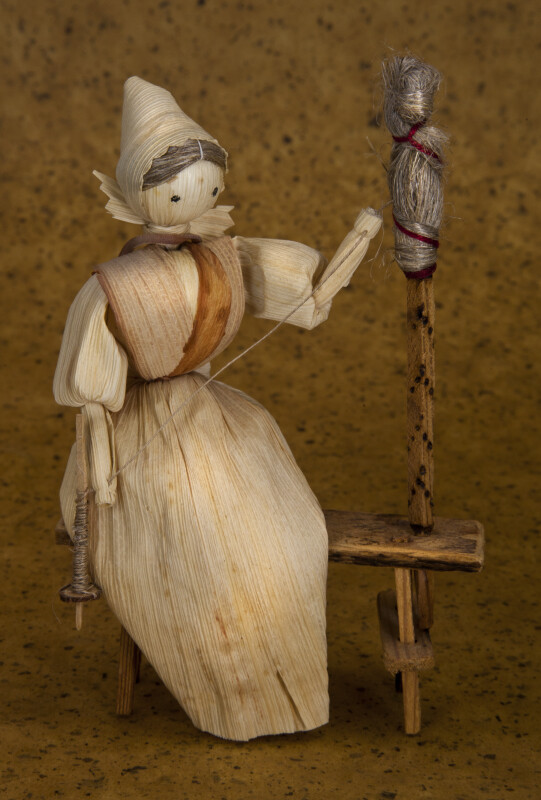 Iowa Cornhusk Woman Sitting on Bench Spinning Wool (Full View)