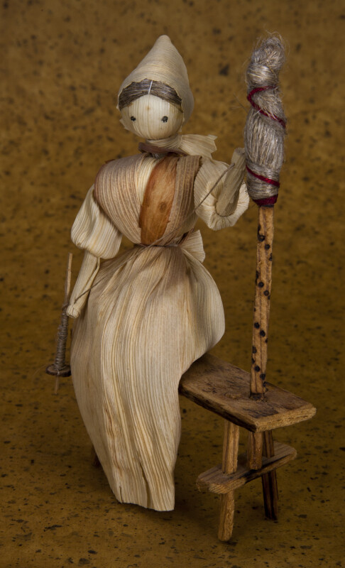 Iowa Woman Made with Corn Husks Sitting on Bench with Spindle (Three Quarter View)