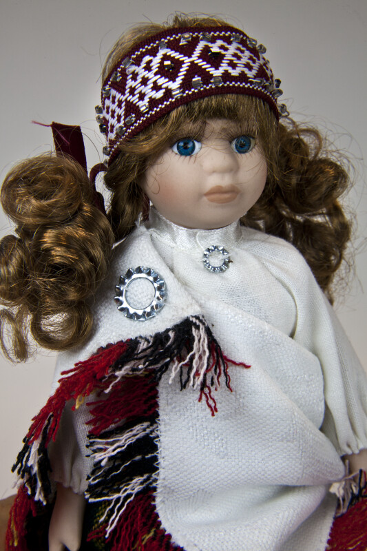 Latvia Girl Wearing Traditional Clothing with Blanket Pinned Over Her Shoulder (Close Up)