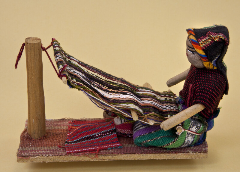 New Mexico Navajo Woman Using Primitive Loom to Weave a Blanket (Profile View)