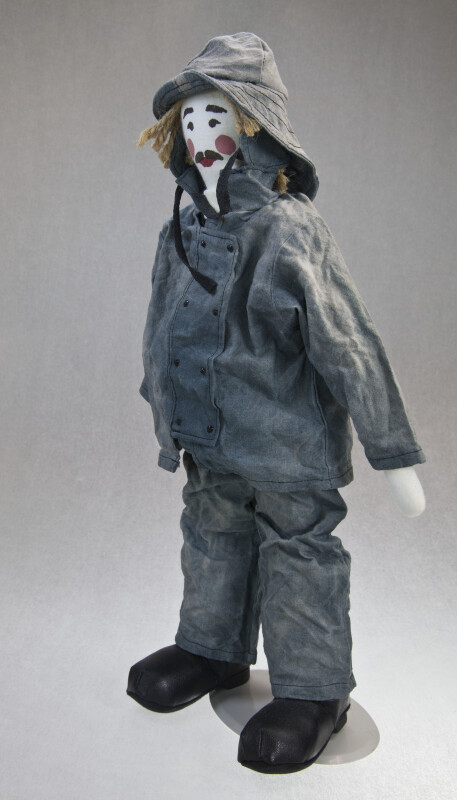 Nova Scotia Fisherman Doll Wearing Oil Cloth Hat, Jacket, and Pants (Three Quarter View)