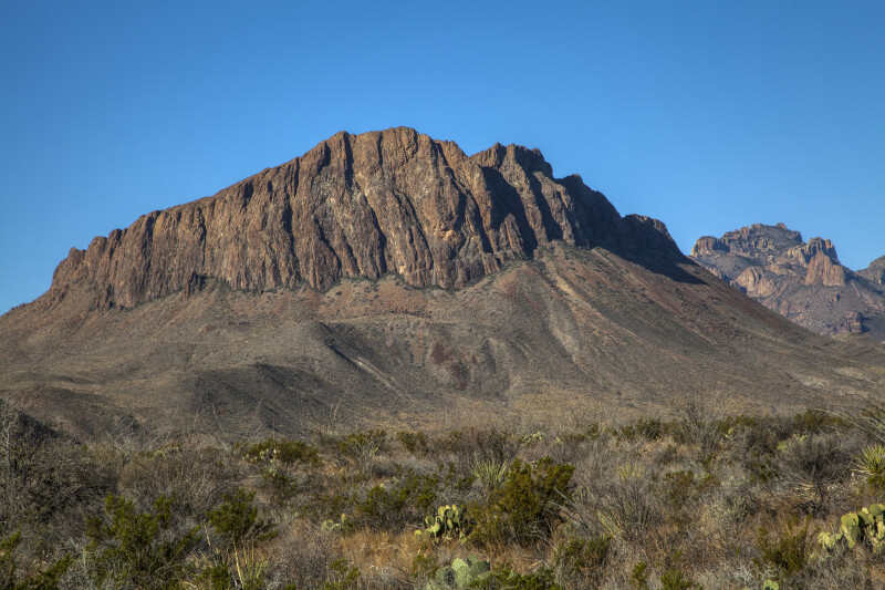 Portion of a Mountain Beyond Dry Desert Shrubs