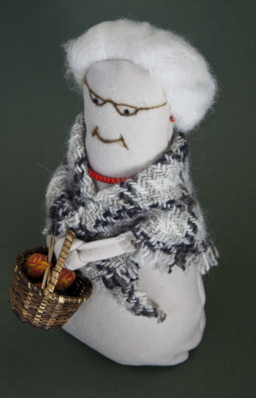 Prince Edward Island Handcrafted Woman Holding a Straw Basket with Balls of Yarn and Knitting Needles (Three Quarter View)