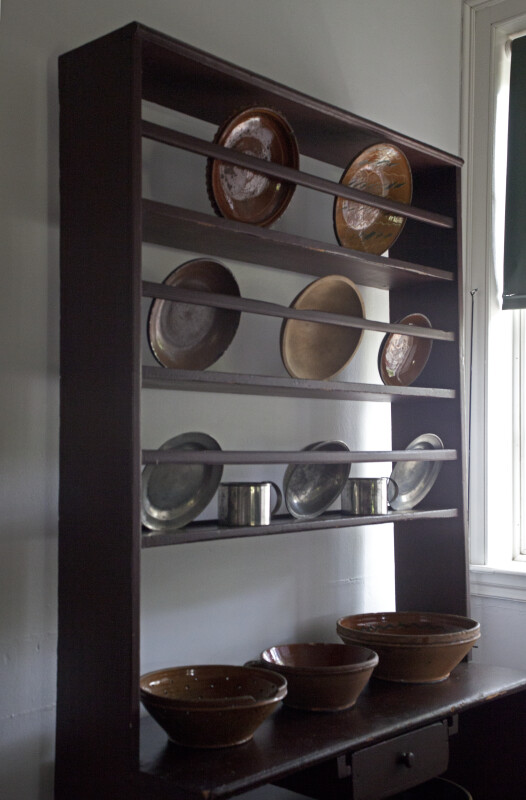 Redware and Tin Dinnerware on a Rack