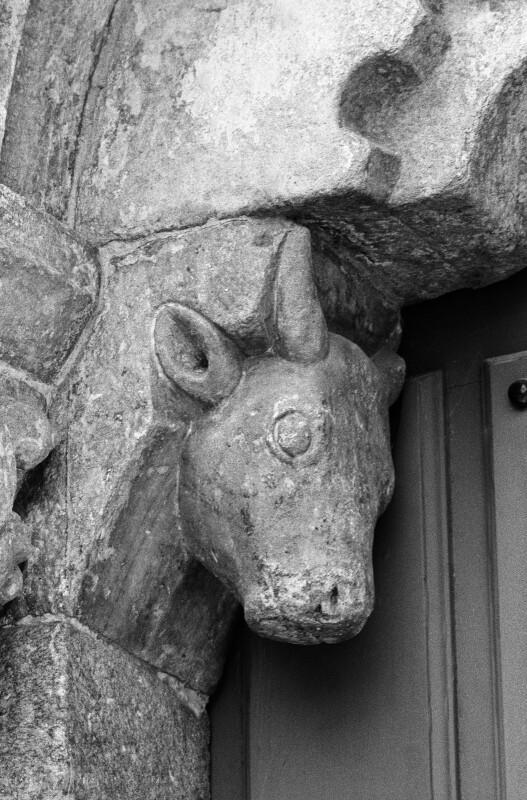 San Pedro de Portomarín, west portal, ox-head corbel beneath tympanum