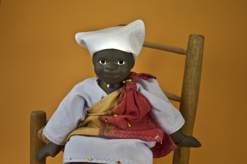 South African Girl with Stuffed Body and Ceramic Extremities (Seated Close Up)