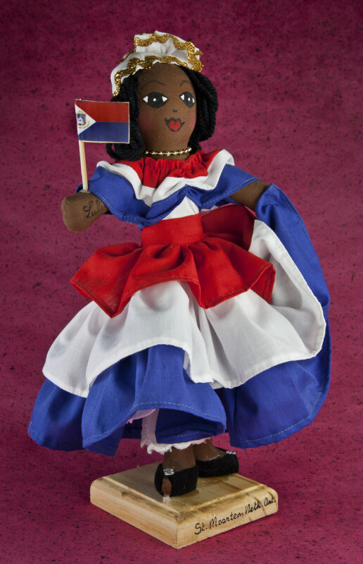 St. Maarten Doll Dressed in Red, White, and Blue, Holding Flag of Dutch Saint Maarten (Three Quarter View)