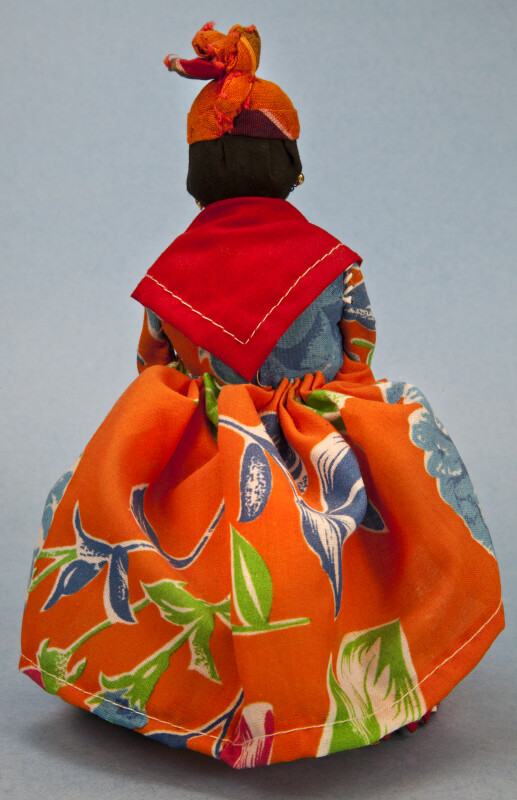US Virgin Islands, St. Thomas Female DollWearing Tropical Dress with Shawl and Head Tie (Back View)