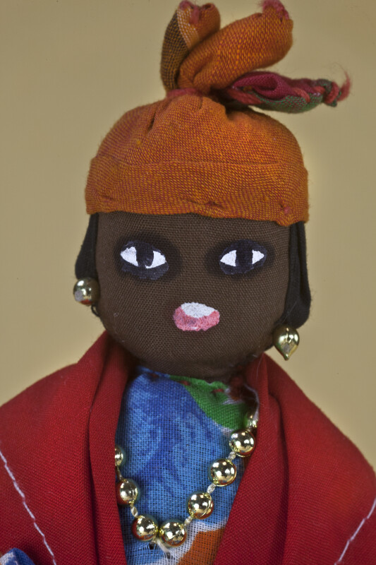 US Virgin Islands, St. Thomas Lady with Hand Painted Facial Features on Fabric (Close Up)