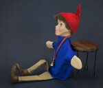 Swiss Boy Puppet Who Is Seated on the Ground  (Side View)