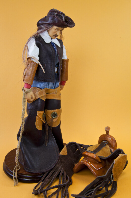Wyoming Cowboy Wearing Leather Vest, Cuffs, Hat and Chaps (Three Quarter View)