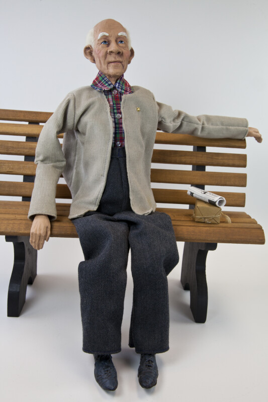 Texas Elderly Male Daddy Long Legs Doll Sitting on a Bench with a Newspaper (Full View)