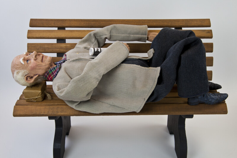 Texas Elderly Man Doll Lying on a Bench with a Newspaper (Lying on Bench)
