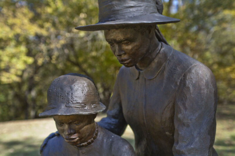 The Faces of Two Bronze Figures That Are Reading a Book