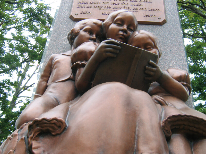 Two Girls and a Boy Reading a Book