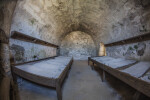 Two Wooden Beds in a Room Adjacent to the Entrance of Castillo de San Marcos