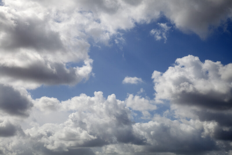White Cumulus Clouds Pictured Against a Light-Blue Sky