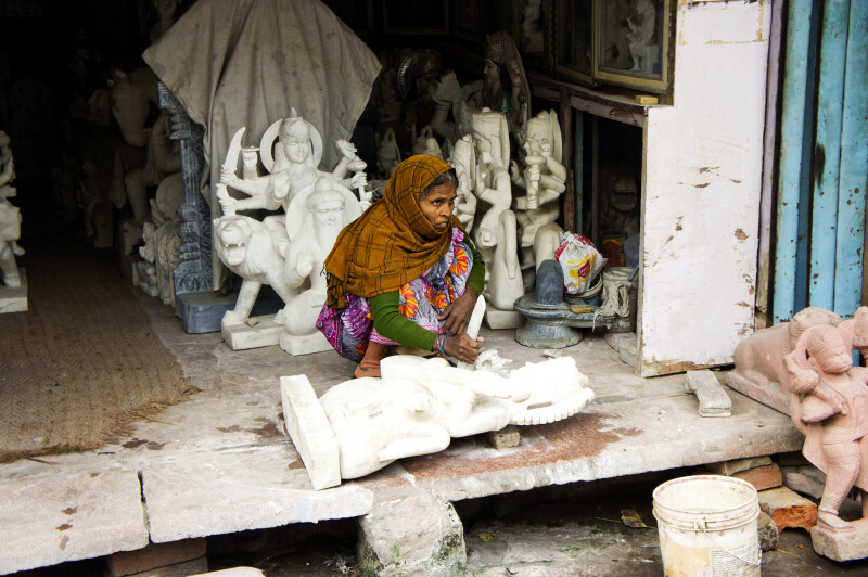 Woman Carving Deity Statue in Marble